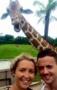Image of couple and smiling giraffe